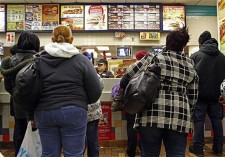 People line up to buy food at a fast food restaurant in Harlem in New York