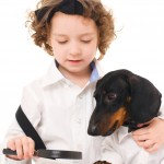 Boy reading to puppy via Shutterstock